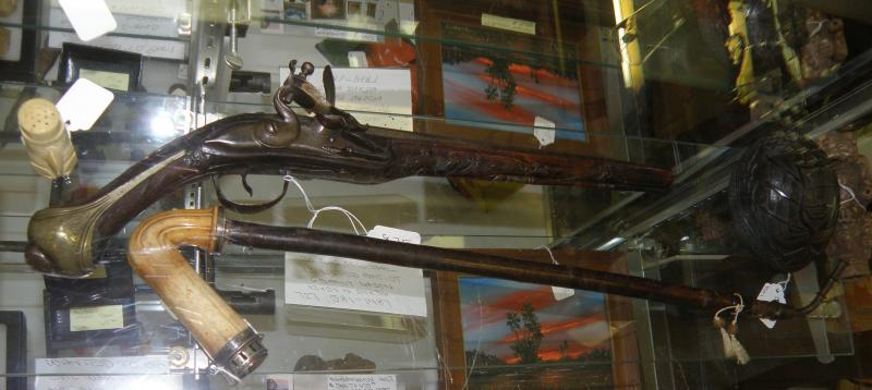 Old Flintlock pistol and opium pipe.